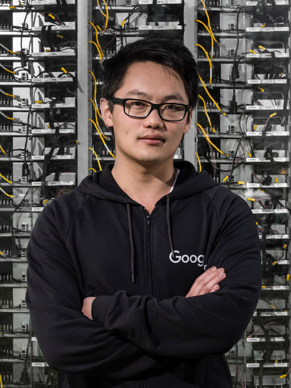 A technician stands in front of a data center wall.