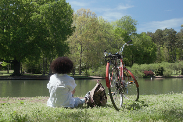 Girl with her bike sitting in the grass overlooking a tree-lined pond on a sunny day.