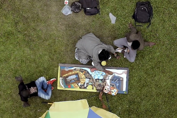 Congolese artist Mugabo works with friends on his mixed media piece.